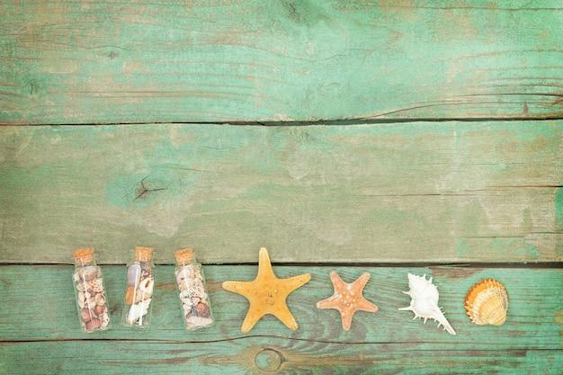 Superfície azul náutica de madeira com conchas, estrelas do mar e pequenas garrafas com conchas