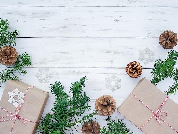 Superfície branca com cones, caixas de presente e galhos de árvores coníferas