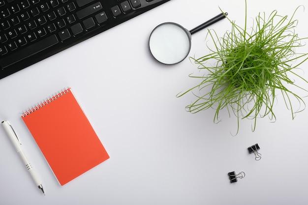 Superfície branca da mesa com teclado, lupa, caderno, clipes, planta de escritório e caneta.