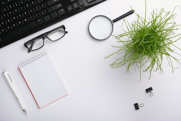 Superfície branca da mesa com teclado, óculos, lupa, caderno, clipes, planta de escritório e caneta.