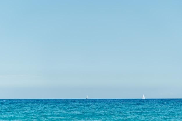 Superfície calma do oceano ou lago ainda com horizonte e céu azul.