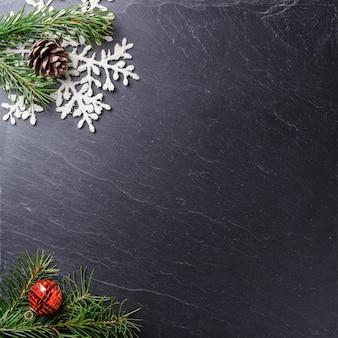 Superfície cinza com ramos de pinheiro ornamentais de natal e um floco de neve com espaço de cópia