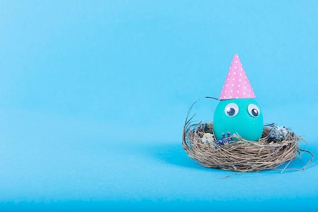 Superfície colorida com ovo de páscoa engraçado fofo na superfície azul