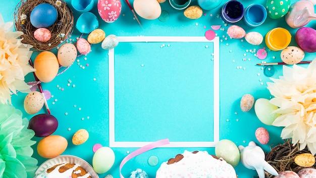 Superfície colorida com ovos de páscoa em uma superfície azul clara
