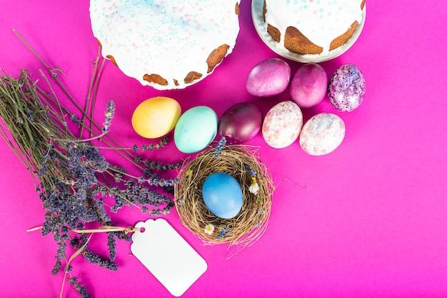 Superfície colorida com ovos de páscoa na superfície rosa