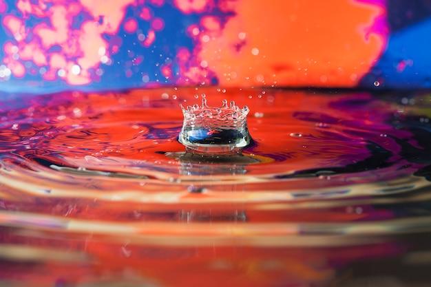 Superfície da água com ondulações e fundo colorido