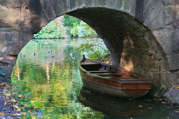 Superfície da água da lagoa com reflexo de árvores coloridas, pássaros nadando e barco sob o arco no parque outono