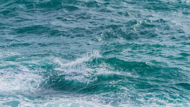 Superfície da água do mar e respingos, água do oceano azul escuro