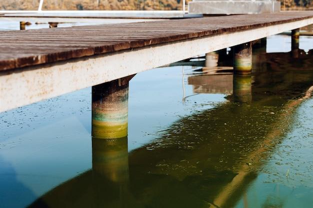 Superfície da água do rio com florescimento de algas nocivas e colunas coloridas de cais de madeira