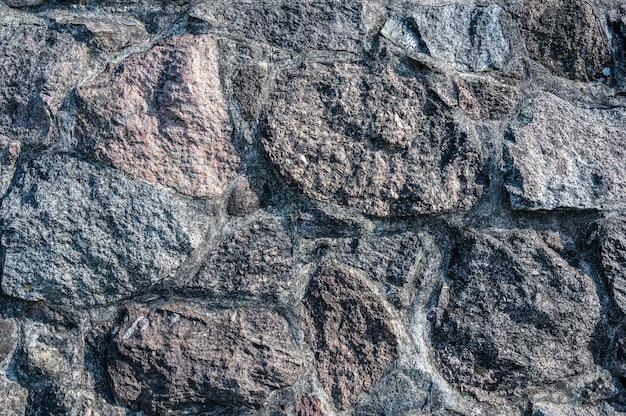 Superfície da parede de grandes pedras texturizadas de granito