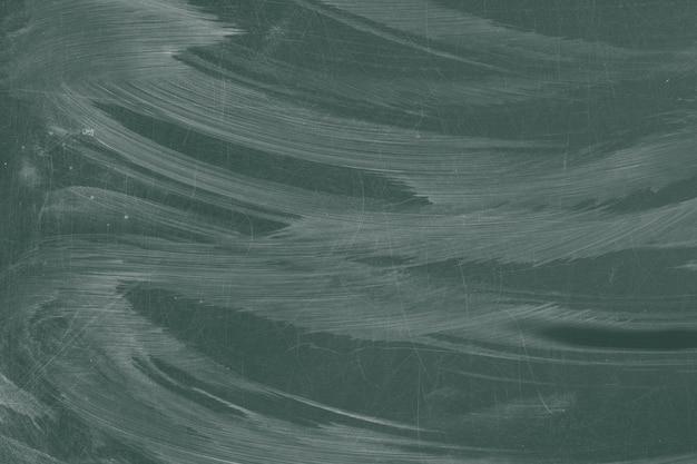 Superfície da placa de giz verde com arranhões e traços de giz molhado
