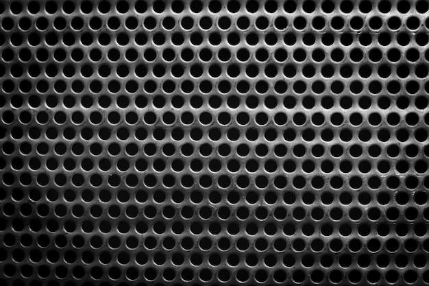 Superfície de aço preto e branco com pequenos furos redondos