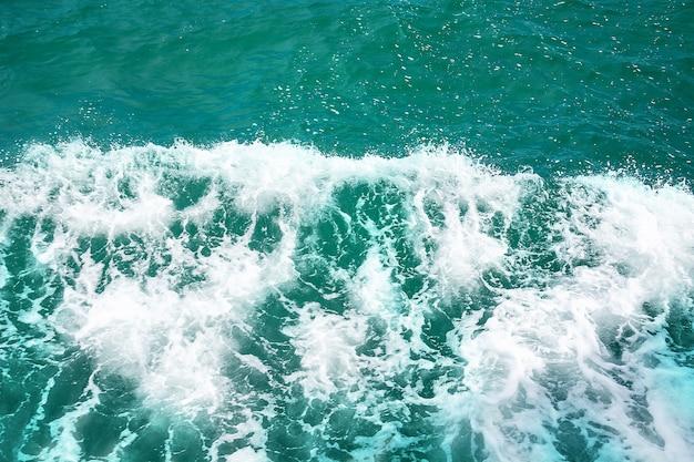 Superfície de água do mar azul profundo com espuma branca e padrão de ondas