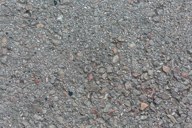 Superfície de cimento com pedras e seixos