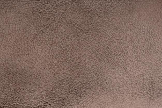 Superfície de couro liso marrom. fundo de textura. fechar-se.