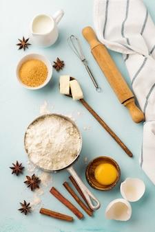 Superfície de cozimento com farinha de ingredientes, ovos, açúcar, manteiga, canela, estrela de anis e utensílios de cozinha na mesa rústica azul. foco seletivo. vista do topo.