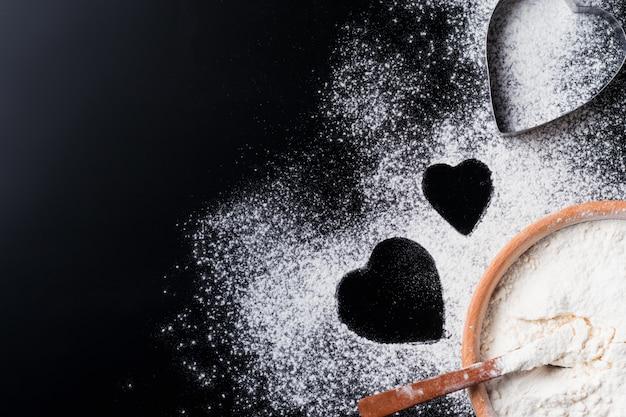 Superfície de cozimento com forma de farinha e coração em uma mesa escura com espaço de cópia, vista superior, plana leigos. dia dos namorados conceito de cozinha