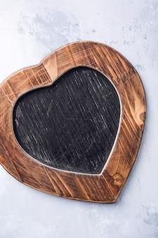 Superfície de dia dos namorados com quadro de giz vintage ardósia em forma de coração com espaço de cópia para o texto. vista de cima