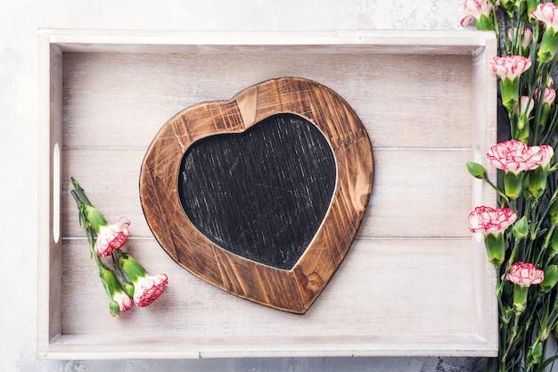 Superfície de dia dos namorados com quadro de giz vintage ardósia em forma de coração e flores rosa cravo com espaço de cópia para o texto. vista de cima