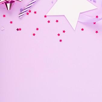 Superfície de festa de feriado com fita, estrelas, velas de aniversário e confetes na superfície rosa