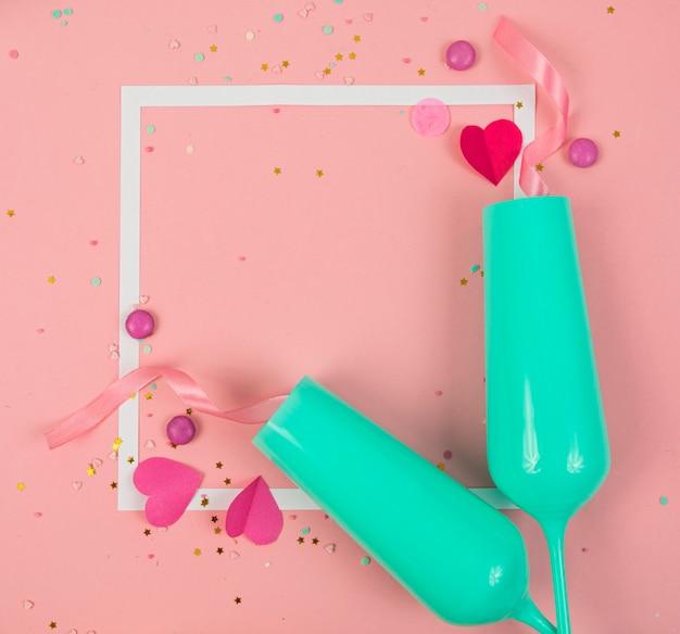 Superfície de festa de feriado com fita, estrelas, velas de aniversário, moldura vazia e confetes na superfície rosa