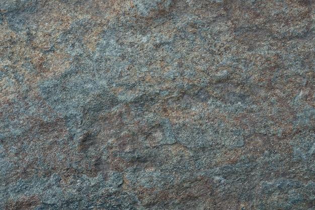 Superfície de granito irregular, cinza e verde.