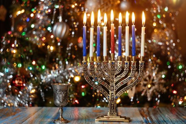 Superfície de hanukkah com menorá e velas acesas na superfície de brilho com luzes desfocadas