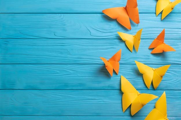Superfície de madeira azul com borboletas de origami de papel colorido com espaço de cópia para o seu texto