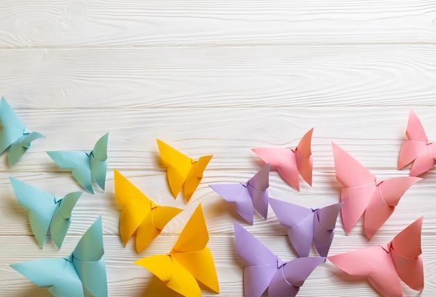 Superfície de madeira branca com borboletas de origami de papel colorido brilhante com espaço de cópia para o seu texto