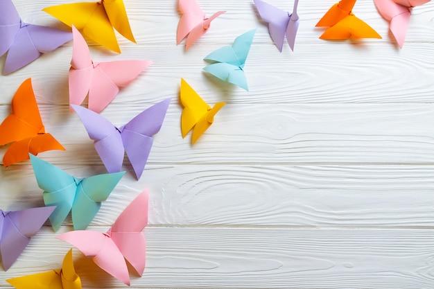 Superfície de madeira branca com um monte de borboletas de origami de papel colorido com espaço de cópia para o seu texto