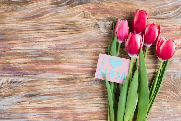 Superfície de madeira com belas flores e cartão para o dia da mãe
