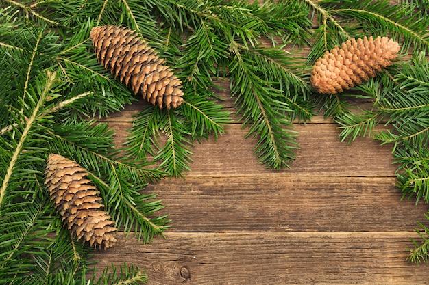 Superfície de madeira com galhos de pinheiro e cones