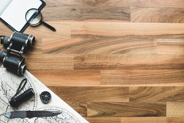 Superfície de madeira com itens de aventura e espaço em branco