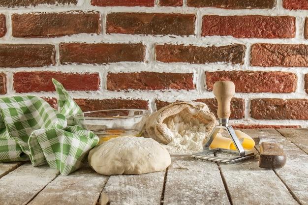Superfície de madeira com massa de pão, toalha de mesa e farinha