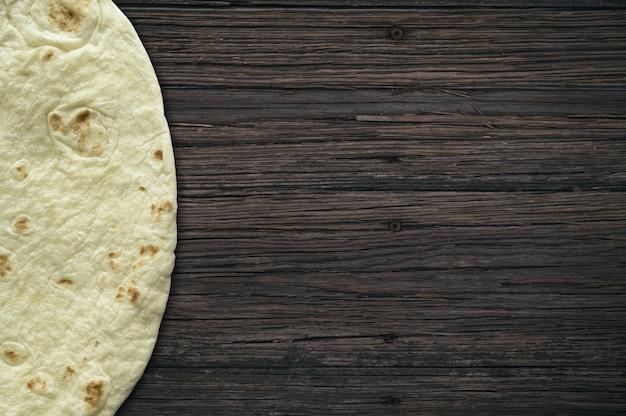 Superfície de madeira com um pão de tortilla ao lado