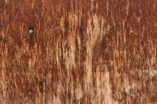 Superfície de madeira desgastada com prego enferrujado