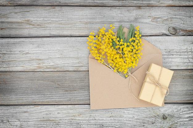 Superfície de madeira ecológica para férias com raminho de envelope de mimosa e caixa para presente
