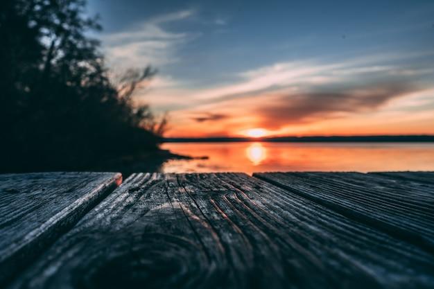 Superfície de madeira no fundo da praia do pôr do sol