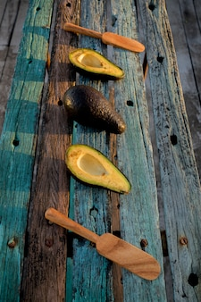 Superfície de madeira rústica com abacates cortados e inteiros e colheres de madeira