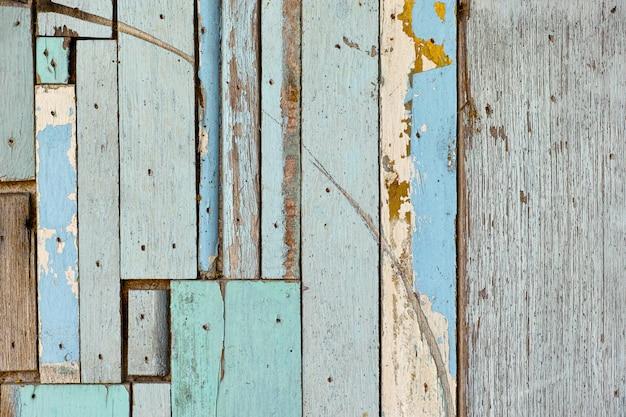 Superfície de madeira velha, verde, azul, lindamente decorado no fundo da parede