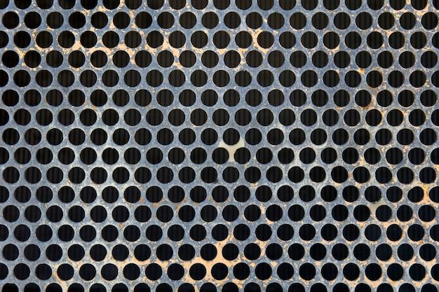 Superfície de metal cinza com buracos redondos pretos