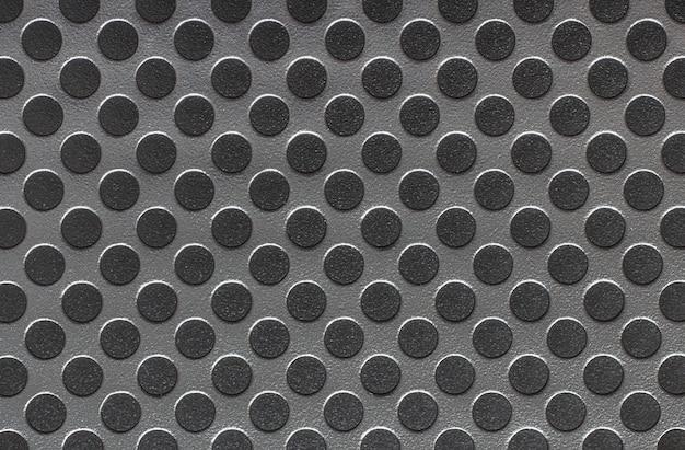 Superfície de metal cinza com círculos pretos.