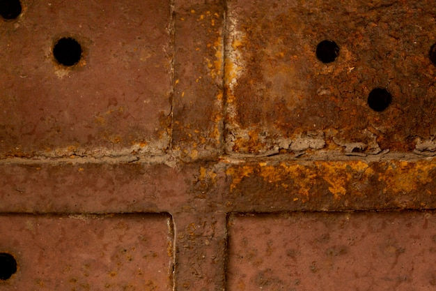 Superfície de metal enferrujada com solda e orifícios
