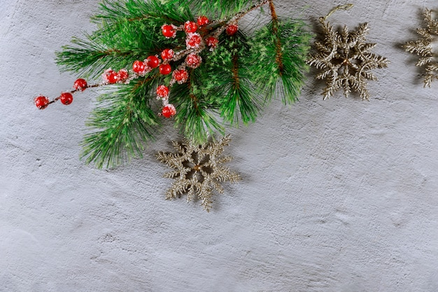 Superfície de natal com abeto branche, bagas vermelhas e flocos de neve