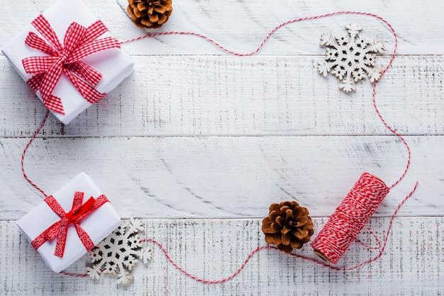 Superfície de natal com fita vermelha, brinquedos, caixas de presente e pinhas na mesa de superfície velha de madeira branca. foco seletivo.