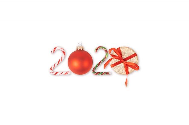 Superfície de natal com números 2020 feitos de bastões de doces, caixas de presente e enfeites de árvore de natal