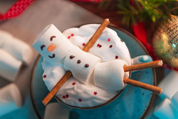 Superfície de natal com um homem de marshmallow deitado em uma caneca com cacau, na superfície uma árvore de natal com brinquedos, uma guirlanda e presentes