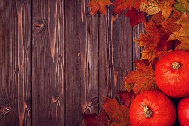 Superfície de outono com folhas coloridas e abóboras na superfície de madeira