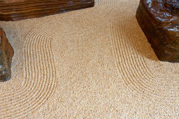 Superfície de pedra de grão pequeno desenhe o padrão como uma curva zen como imagem de fundo.