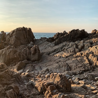 Superfície de rocha áspera com sombras de luz do sol e vista do mar e do céu azul